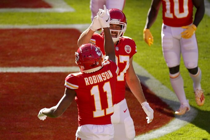 Kansas City Chiefs' Demarcus Robinson (11) and Travis Kelce (87) celebrate a touchdown scored by Robinson on a catch in the second half of an NFL football game against the New York Jets on Sunday, Nov. 1, 2020, in Kansas City, Mo. (AP Photo/Charlie Riedel)