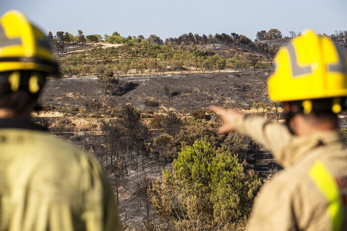 Two firefighters look at burned terrain in La Palma d'Ebre, Spain, Friday June 28, 2019. A major wildfire in northeastern Spain that began in a pile of chicken dung raged out of control for a third straight day Friday with more than 600 firefighters and six water-dropping aircraft battling the blaze in the Catalonia region. Spain is forecast to endure the peak of a recent heat wave, with temperatures expected to exceed 40 degrees Celsius (104 Fahrenheit). (AP Photo/Jordi Borras)