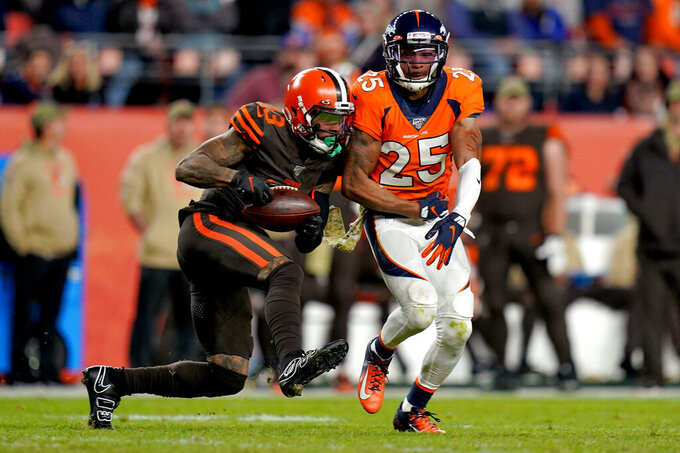 Cleveland Browns wide receiver Odell Beckham (13) pulls in a catch as Denver Broncos cornerback Chris Harris (25) defends during the second half of an NFL football game against the Cleveland Browns, Sunday, Nov. 3, 2019, in Denver. The Broncos won 24-19. (AP Photo/Jack Dempsey)