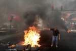 An anti-government protester sets fire on tires to block a road during a protest against government's plans to impose new taxes in Beirut, Lebanon, Friday, Oct. 18, 2019. The protests erupted over the government's plan to impose new taxes during a severe economic crisis, with people taking their anger out on politicians they accuse of corruption and decades of mismanagement. (AP Photo/Hassan Ammar)