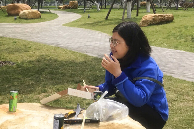 In this photo taken April 14, 2020 and released by Melanie Wang, Zhang Zhan eats a meal at a park during a visit to Wuhan in central China's Hubei province. A Chinese court on Monday sentenced the former lawyer who reported on the early stage of the coronavirus outbreak to four years in prison on charges of