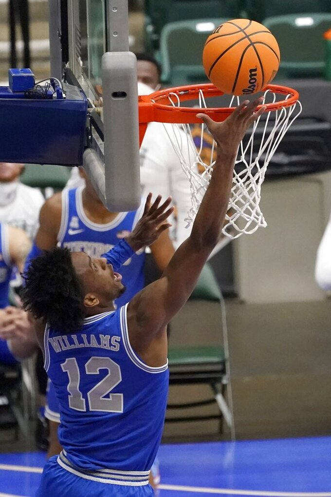 Memphis forward DeAndre Williams (12) leans in from behind the basket to sink a shot in the3 second half of an NCAA college basketball game against Colorado State in the semifinals of the NIT, Saturday, March 27, 2021, in Frisco, Texas. (AP Photo/Tony Gutierrez)