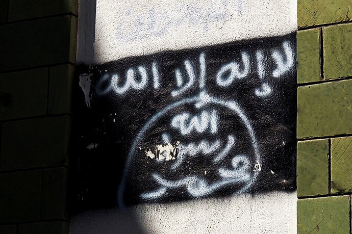 FILE - This Oct. 16, 2017, file photo shows the black al-Qaida flag is sprayed on the wall of a damaged school that was turned into a religious court, in Taiz, Yemen. President Donald Trump said Thursday, Feb. 6, 2020, that the U.S. at his direction has conducted a counter-terrorism operation in Yemen that killed Qassim al-Rimi, an al-Qaida leader who claimed responsibility for last year's deadly shooting at the Naval Air Station Pensacola where a Saudi aviation trainee killed three American sailors. (AP Photo, File)