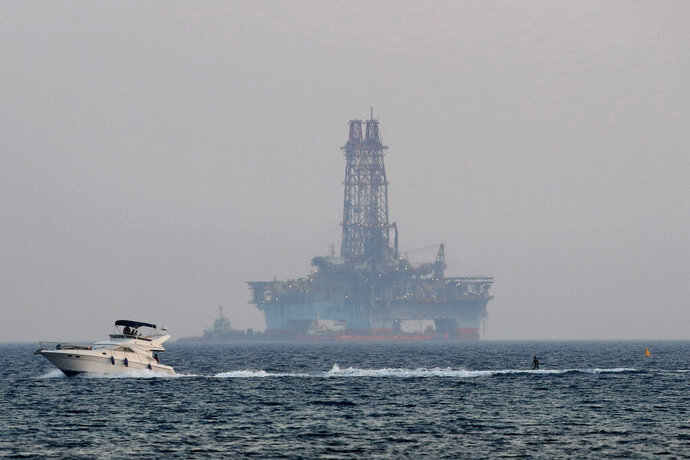 An offshore drilling rig is seen in the waters off Cyprus' coastal city of Limassol, Sunday, July 5, 2020 as a boat passes with a skier. Russian President Vladimir Putin has promised to intercede with Turkey to try and ease rising tensions over its oil and gas exploration in eastern Mediterranean waters that Cyprus claims as its own, the Cypriot government said Thursday, July 30, 2020. (AP Photo/Petros Karadjias)