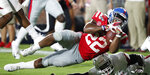 Mississippi running back Scottie Phillips (22) dives over Arkansas defensive back Joe Foucha for short yards during the second half of an NCAA college football game Saturday, Sept. 7, 2019, in Oxford, Miss. Mississippi won 31-17. (AP Photo/Rogelio V. Solis)