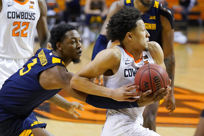 West Virginia forward Gabe Osabuohien (3) reaches in to try and knock the ball away as Oklahoma State guard Cade Cunningham, right, drives past him in the second half of an NCAA college basketball game Monday, Jan. 4, 2021, in Stillwater, Okla. (AP Photo/Sue Ogrocki)