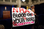 FILE - In this Dec. 21, 2012, file photo, activist Medea Benjamin, of Code Pink, is led away by security as she protests during a statement by National Rifle Association executive vice president Wayne LaPierre, left, during a news conference in response to the Connecticut school shooting in Washington. In the latest national furor over mass killings, the tremendous political power of the NRA is likely to stymie any major changes to gun laws. The man behind the organization is LaPierre, the public face of the Second Amendment with his bombastic defense of guns, freedom and country in the aftermath of every mass shooting. (AP Photo/ Evan Vucci, File)