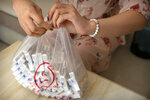 A woman holds a plastic bag of OxyContin tablets sold in China in southern China's Hunan province on Sept. 24, 2019. Representatives from the Sacklers' Chinese affiliate, Mundipharma, tell doctors that OxyContin is less addictive than other opioids — the same pitch that their U.S. company, Purdue Pharma, admitted was false in court more than a decade ago. (AP Photo/Mark Schiefelbein)