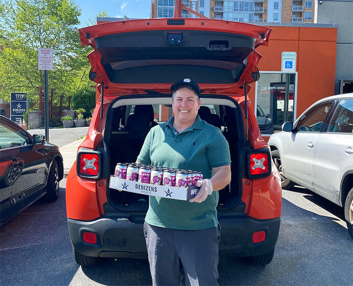 In this May 15, 2020, photo, provided by Brian Coulombe, Julie Verratti, one of the co-founders of Denizens Brewing Company, holds a case of beers for delivery in Silver Spring, Md. The brewing company has been delivering beers to customers in the area while its taprooms are closed amid the coronavirus pandemic. (Brian Coulombe/Denizens Brewing Company via AP)