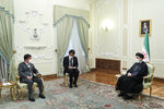 In this photo released by the official website of the office of the Iranian Presidency, President Ebrahim Raisi, right, and Japanese Foreign Minister Toshimitsu Motegi, left, meet at the presidency office, in Tehran, Iran, Sunday, Aug. 22, 2021. An unidentified interpreter sits at center. (Iranian Presidency Office via AP)