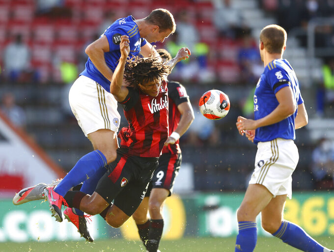 Leicester's Jonny Evans, left, heads the ball away from Bournemouth's Nathan Ake during the English Premier League soccer match between Bournemouth and Leicester City at Vitality Stadium in Bournemouth, England, Sunday, July 12, 2020. (AP Photo/Michael Steele,Pool)