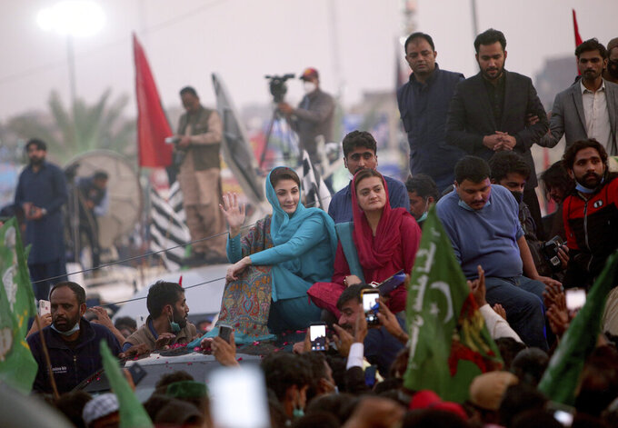 Maryam Nawaz Sharif, center, in blue dress, a leader of the Pakistan Democratic Movement, an alliance of opposition parties, waves to her supporter during an anti-government rally, in Multan, Pakistan, Monday, Nov. 30, 2020. Despite a government ban and arrests of hundreds of activists, Pakistani opposition supporters rallied in a central city on Monday, calling on Prime Minister Imran Khan to resign over alleged bad governance and incompetence. (AP Photo/Asim Tanveer)