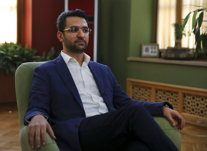 FILE — In this July 7, 2019 file photo, Iran's telecommunications Minister Mohammad Javad Azari Jahromi sits in his office in Tehran, Iran. Iran's judiciary released Jahromi on bail Wednesday, Jan. 20, 2021 after he was summoned for prosecution by Iran's general prosecutor, state TV reported. Jamal Hadian, a spokesman for the telecommunications ministry, was quoted as saying Jahromi appeared before a prosecutor Wednesday, was released and had already returned to his office. (AP Photo/Vahid Salemi, File)