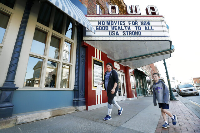 Mesha Wagner, of Winterset, Iowa, and her son Karsen Keller, right, walk past the Iowa Theater that is closed in response to the coronavirus outbreak, Wednesday, April 1, 2020, in Winterset, Iowa. The new coronavirus causes mild or moderate symptoms for most people, but for some, especially older adults and people with existing health problems, it can cause more severe illness or death. (AP Photo/Charlie Neibergall)