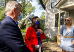 ADDS NAME OF SUBJECT AT RIGHT - Michigan Gov. Gretchen Whitmer, center, and legislative candidate Dan O'Neil, left, greet Rachel White in Traverse City, Mich., Friday, Oct. 9, 2020. Whitmer visited the area the day after police announced a foiled plot to kidnap the governor. (AP Photo/John Flesher)