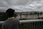 A man watches the flooded park near the Han River in Seoul, South Korea, Thursday, Aug. 6, 2020. The state-run Han River Flood Control Office issued a flood alert near a key river bridge in Seoul, the first such advisory since 2011. (AP Photo/Lee Jin-man)
