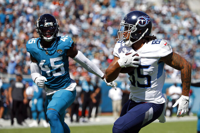 Tennessee Titans tight end MyCole Pruitt runs for a touchdown past Jacksonville Jaguars linebacker K'Lavon Chaisson (45) during the first half of an NFL football game, Sunday, Oct. 10, 2021, in Jacksonville, Fla. (AP Photo/Stephen B. Morton)