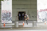 A worker washes graffiti off the sidewalk in front of the Mark O. Hatfield Federal Courthouse in downtown Portland, Ore., on Wednesday, July 8, 2020, as two agents with the U.S. Marshals Service emerge from the boarded-up main entrance to examine the damage. Protesters who have clashed with authorities in Portland, Ore., are facing off not just against city police but a contingent of federal agents who reflect a new priority for the Department of Homeland Security: preventing what President Donald Trump calls