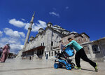 In this photo taken on Tuesday, Aug. 20, 2019, a Syrian boy pushes a pram past Fatih mosque in Istanbul. Syrians say Turkey has been detaining and forcing some Syrian refugees to return back to their country the past month. The expulsions reflect increasing anti-refugee sentiment in Turkey, which opened its doors to millions of Syrians fleeing their country's civil war. (AP Photo/Lefteris Pitarakis)
