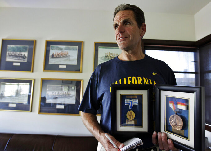 FILE - In this May 7, 2012, file photo, coach Mike Teti displays the bronze medal from the Seoul Olympics and the gold medal from the 1987 World Championship in Copenhagen in his office in Oakland, Calif. Longtime U.S. rowing coach Teti, who has been criticized by some of his former team members as being emotionally abusive and using physical intimidation, has resigned but immediately accepted a position funded by a large donor leading a new high-performance training club ahead of the 2024 Olympics in Paris. (AP Photo/Paul Sakuma, File)