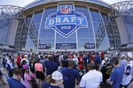 FILE - In this April 27, 2018, file photo, people wait to get into the stadium for the second round of the NFL football draft in Arlington, Texas. The NFL is partnering with Caesars Entertainment as its first official casino sponsor, but the deal does not include sports betting or fantasy football. The multiyear arrangement announced Thursday, Jan. 3, 2019, begins with this weekend's playoffs. Caesars will have exclusive rights to NFL trademarks in the U.S. and United Kingdom, including the Super Bowl and draft. Caesars will host parts of the 2020 draft. (Paul Moseley/Star-Telegram via AP, File)
