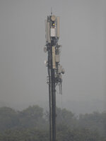 An Indian technician works atop a cellular tower in New Delhi, India, Friday, Nov. 1, 2019. An expert panel in India's capital declared a health emergency Friday due to air pollution choking the city, with authorities ordering schools closed until Nov. 5. (AP Photo/Altaf Qadri)