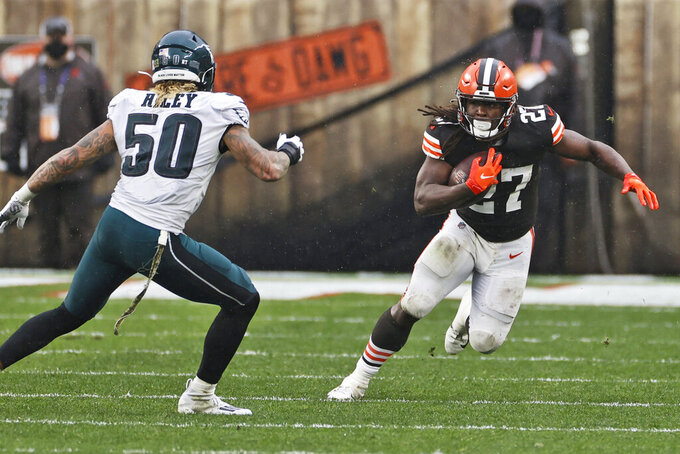 Cleveland Browns running back Kareem Hunt (27) avoids a tackle by Philadelphia Eagles middle linebacker Duke Riley (50) during the first half of an NFL football game, Sunday, Nov. 22, 2020, in Cleveland. (AP Photo/Ron Schwane)
