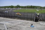 A fan watches as cars practice on a short dirt track at Gas City I-69 Speedway, Sunday, May 24, 2020, in Gas City, Ind. (AP Photo/Darron Cummings)