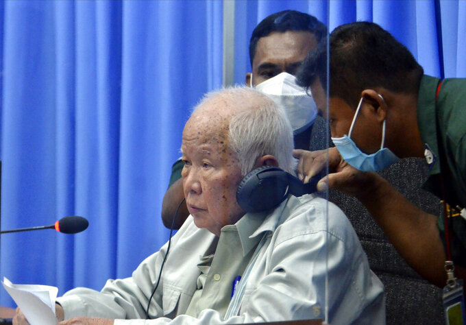 In this photo released by the Extraordinary Chambers in the Courts of Cambodia, Khieu Samphan, left,  the former head of state for the Khmer Rouge, sits in a courtroom during a hearing at the U.N.-backed war crimes tribunal in Phnom Penh, Cambodia, Thursday, Aug. 19, 2021. The last living member of former Cambodian leader Pol Pot's inner circle denied complicity in the genocide committed under the brutal Khmer Rouge government, telling an international tribunal hearing his appeal Thursday that he was being judged as a proxy for the entire radical communist regime. (Mark Peters/Extraordinary Chambers in the Courts of Cambodia via AP)