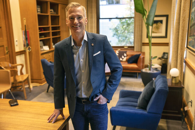 FILE - In this Oct. 9, 2020, file photo, Mayor Ted Wheeler poses in a City Hall office in Portland, Ore. Mayor Wheeler is facing Sarah Iannarone in the election on Tuesday, Nov. 3, 2020. (AP Photo/Paula Bronstein, File)