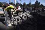 Volunteers dismantle a barricade in a major cleanup effort in the aftermath of violent protests against the government, in Quito, Ecuador, Monday, Oct. 14, 2019. Ecuador celebrated a deal President Lenín Moreno and indigenous leaders struck late Sunday to cancel a disputed austerity package and end nearly two weeks of protests that have paralyzed the economy and left seven dead. (AP Photo/Fernando Vergara)