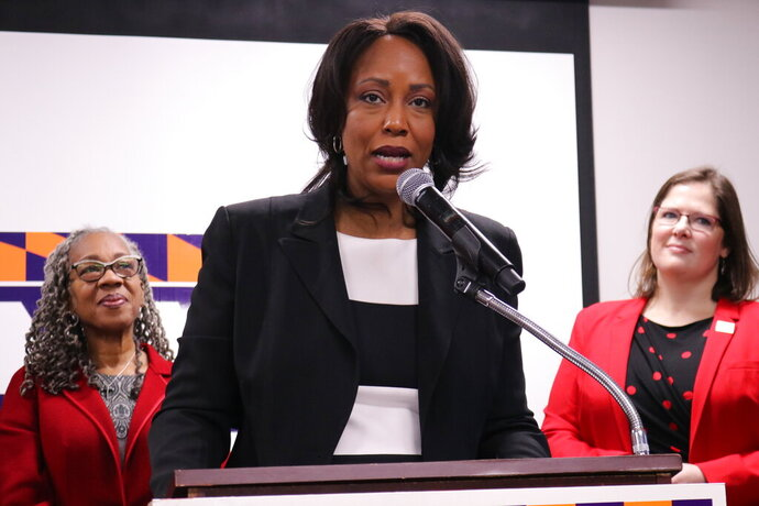 In this Jan. 27, 2020 photo, Maya Rockeymoore Cummings, who is running for her late husband's congressional seat in a special primary in Maryland, speaks at a news conference in Baltimore, Md. Emily Cain, executive director of EMILY's List, is standing right. Helen Holton, a former Baltimore City Councilwoman, is standing left. AP Photo/Brian Witte)
