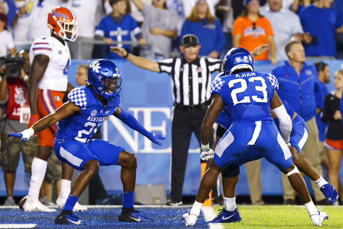Kentucky's defense celebrates after stopping Florida on a fourth down to win their NCAA college football game in Lexington, Ky., Saturday, Oct. 2, 2021. (AP Photo/Michael Clubb)