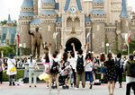 Visitors wave to Disney characters performing at Tokyo Disneyland in Urayasu, near Tokyo, Wednesday, July 1, 2020. Tokyo Disneyland reopened for the first time in four months after suspending operations due to coronavirus concerns. (Kyodo News via AP)