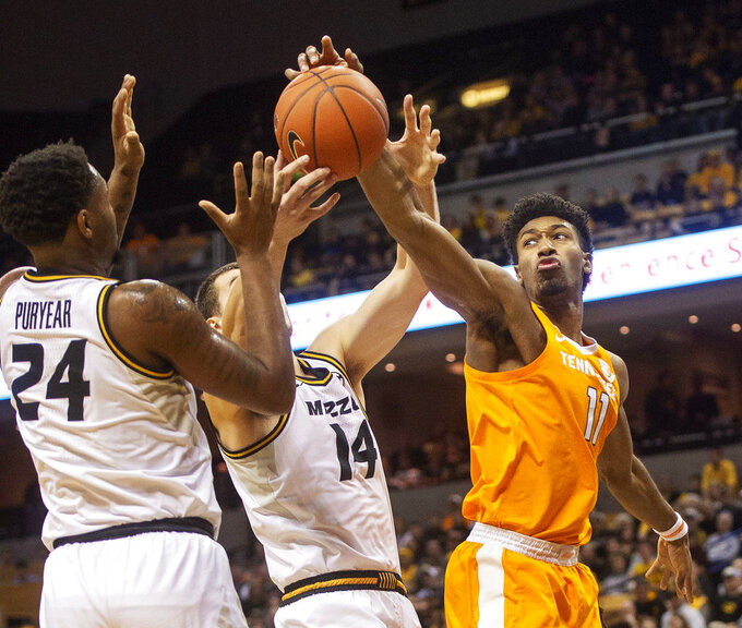 Tennessee's Kyle Alexander, right, Missouri's Kevin Puryear, left, and Reed Nikko, center battle for a rebound during the first half of an NCAA college basketball game Tuesday, Jan. 8, 2019, in Columbia, Mo. (AP Photo/L.G. Patterson)