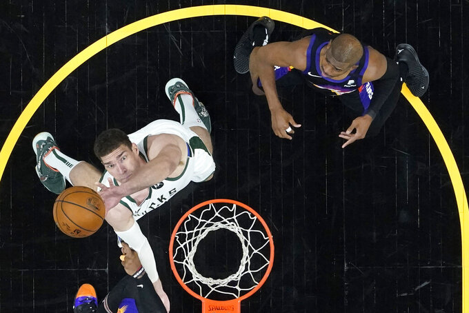Milwaukee Bucks center Brook Lopez rebounds as Phoenix Suns guard Chris Paul, right, looks on during the first half of Game 1 of basketball's NBA Finals, Tuesday, July 6, 2021, in Phoenix. (AP Photo/Matt York, Pool)