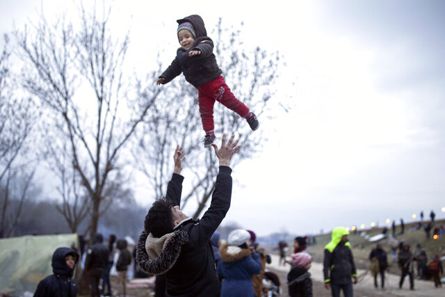 A migrant throws a baby in the air in Edirne near the Turkish-Greek border on Thursday, March 5, 2020. Turkey said Thursday it would deploy special forces along its land border with Greece to prevent Greek authorities from pushing back migrants trying to cross into Europe, after Turkey declared its previously guarded gateways to Europe open. (AP Photo/Emrah Gurel)