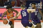 Illinois guard Ayo Dosunmu (11) powers past Northwestern's forward Miller Kopp (10) and guard Anthony Gaines (11) in the first half of an NCAA college basketball game Tuesday, Feb. 16, 2021, in Champaign, Ill. (AP Photo/Holly Hart)