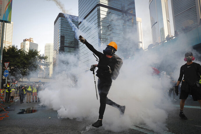An anti-government protester throws back a tear gas canister fired by the police during a demonstration near Central Government Complex in Hong Kong, Sunday, Sept. 15, 2019. Police fired a water cannon and tear gas at protesters who lobbed Molotov cocktails outside the Hong Kong government office complex Sunday, as violence flared anew after thousands of pro-democracy supporters marched through downtown in defiance of a police ban. (AP Photo/Kin Cheung)