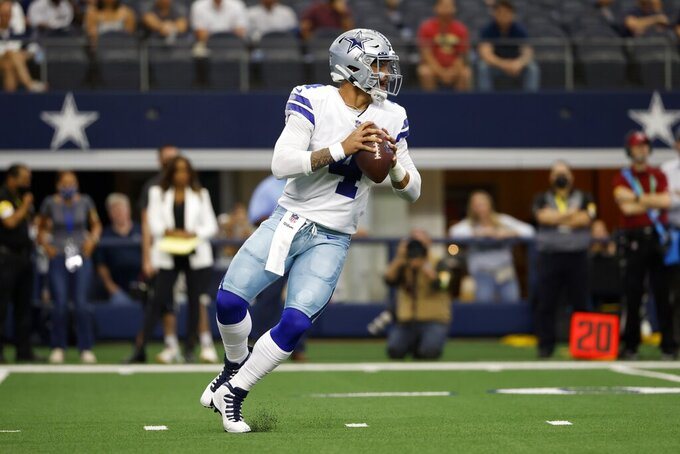 Dallas Cowboys quarterback Dak Prescott drops back to pass in the first half of a NFL football game against the Carolina Panthers in Arlington, Texas, Sunday, Oct. 3, 2021. (AP Photo/Ron Jenkins)