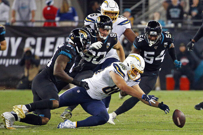 Los Angeles Chargers tight end Hunter Henry, right, recovers a Philip Rivers fumble in front of Jacksonville Jaguars defensive end Yannick Ngakoue, left, defensive tackle Taven Bryan (90) and linebacker Donald Payne (54) during the second half of an NFL football game, Sunday, Dec. 8, 2019, in Jacksonville, Fla. (AP Photo/Stephen B. Morton)