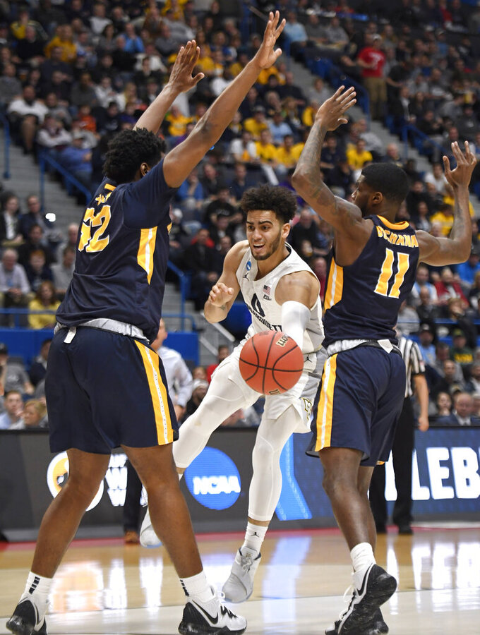 Marquette's Markus Howard (0) passes between Murray State's Darnell Cowart (32) and Murray State's Shaq Buchanan (11) during the first half of a first round men's college basketball game in the NCAA tournament, Thursday, March 21, 2019, in Hartford, Conn. (AP Photo/Jessica Hill)