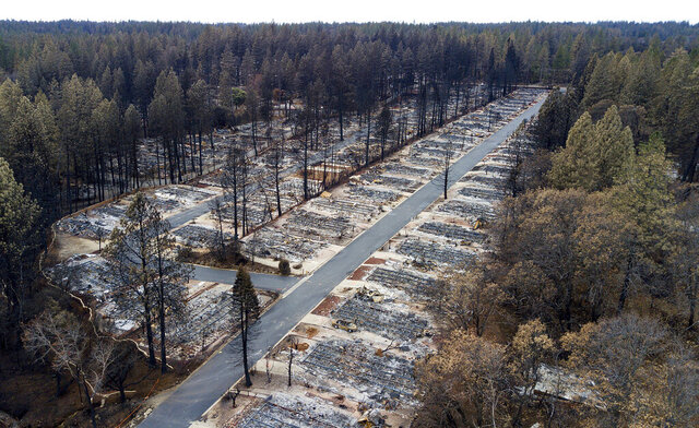 FILE - This Dec. 3, 2018, file photo shows homes leveled by the Camp Fire line at the Ridgewood Mobile Home Park retirement community in Paradise, Calif. Lawyers who negotiated a deal between wildfire victims and Pacific Gas & Electric say questions about the beleaguered company's ability to pay $13.5 billion to the victims could unravel the deal, upending the company's efforts to get out of bankruptcy by June 30.(AP Photo/Noah Berger, File)