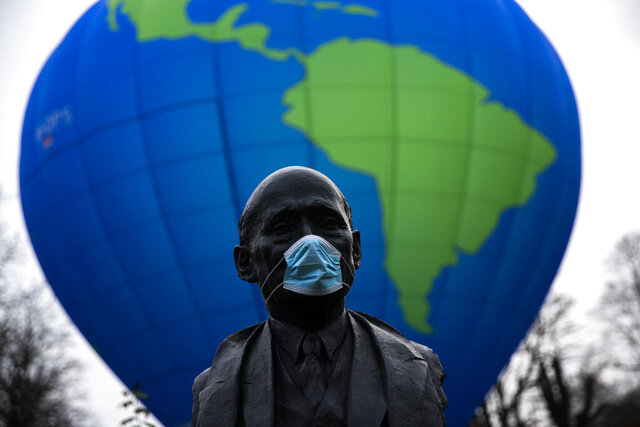 The bust of French statesman Robert Schuman, one of the founders of the European Union, is seen while environmental activists launch a hot air balloon during a demonstration outside of an EU summit in Brussels, Thursday, Dec. 10, 2020. European Union leaders meet for a year-end summit that will address anything from climate, sanctions against Turkey to budget and virus recovery plans. Brexit will be discussed on the sidelines. (AP Photo/Francisco Seco)