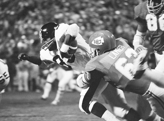 "FILE - In this Oct. 19, 1971, file photo, Pittsburgh Steelers' John Fuqua (33) is brought down Kansas City Chiefs' Willie Lanier after a 3-yard game during an NFL football game in Kansas City, Mo. Lanier was one of the first black middle linebackers in pro football, breaking a barrier that kept minorities from playing the position regarded as the ""quarterback of the defense."" Lanier was a key part of the Kansas City defense that dominated the AFL and won a Super Bowl following the 1969 season. (AP Photo/William Straeter, File)"