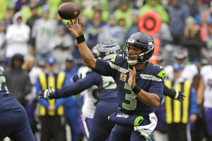 Seattle Seahawks quarterback Russell Wilson passes against the Baltimore Ravens during the first half of an NFL football game, Sunday, Oct. 20, 2019, in Seattle. (AP Photo/Elaine Thompson)