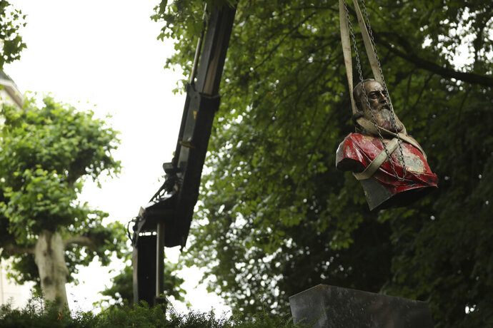 A bust of Belgium's King Leopold II, is hoisted off of its plinth by a crane as it's removed from a park in Ghent, Belgium on Tuesday, June 30, 2020. Protests sweeping the world after George Floyd's death in the U.S. have added fuel to a movement to confront Europe's role in the slave trade and its colonial past. Leopold II is increasingly seen as a stain on the nation where he reigned from 1865 to 1909 with some demonstrators calling for his removal from public view. (AP Photo/Francisco Seco)
