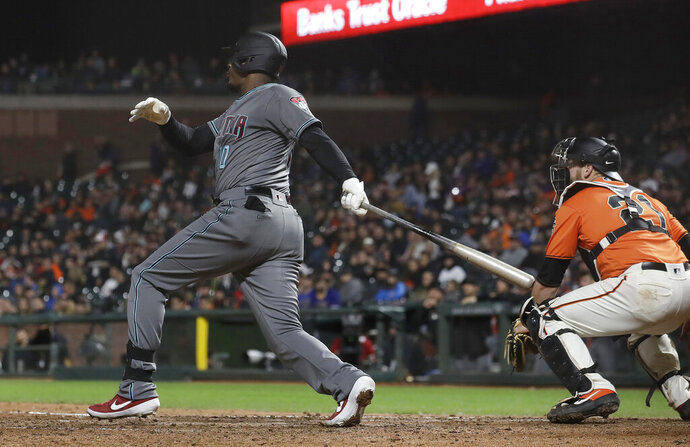 Arizona Diamondbacks' Adam Jones watches his three-run home run in front of San Francisco Giants catcher Stephen Vogt during the fifth inning of a baseball game in San Francisco, Friday, May 24, 2019. (AP Photo/Jeff Chiu)