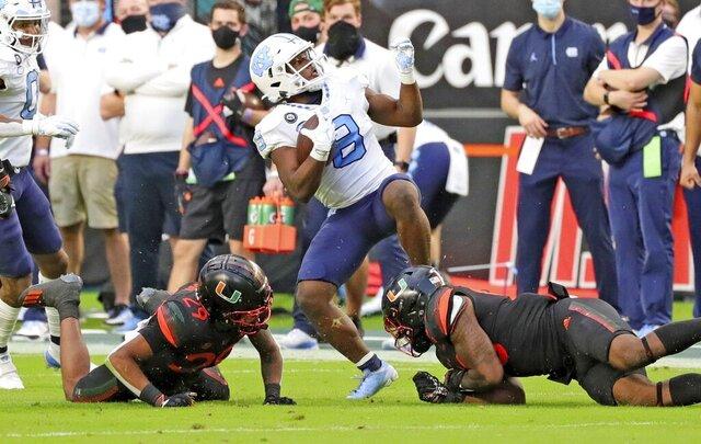 Miami linebacker Zach McCloud (53) and cornerback Isaiah Dunson (29) stop North Carolina running back Michael Carter (8) during the first half of an during an NCAA college football game at Hard Rock Stadium In Miami Gardens, Fla, Saturday, Dec, 12, 2020. (Al Diaz/Miami Herald via AP)