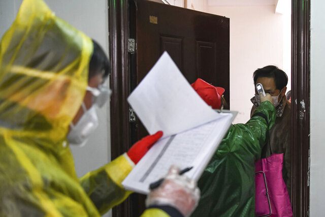 In this Feb. 18, 2020, photo released by Xinhua News Agency, workers go door to door to check the temperature of residents during a health screening campaign in the Qingheju Community, Qingshan District of Wuhan in central China's Hubei Province. Protective suit-clad inspectors in the epicenter of China's viral outbreak went door-to-door to find every infected person in the central city suffering most from an epidemic that is showing signs of waning as new cases fell for a second day. (Cheng Min/Xinhua via AP)